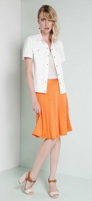 Camisa branca de mangas curtas em tecido mais estruturado usada aberta sobre saia de malha alaranjada evasé na altura dos joelhos. Por baixo, uma camiseta regata em tecido compõe o visual.