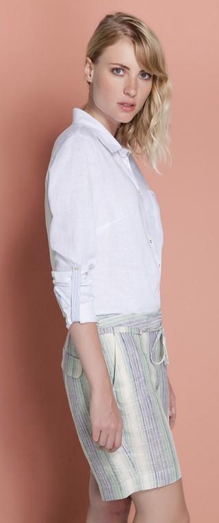 Camisa branca de mangas longa arregaçadas presas no cotovelo por uma alça do mesmo tecido. Usada com uma bermuda de linho com listras finas em tons suaves de azul, creme e verde água.