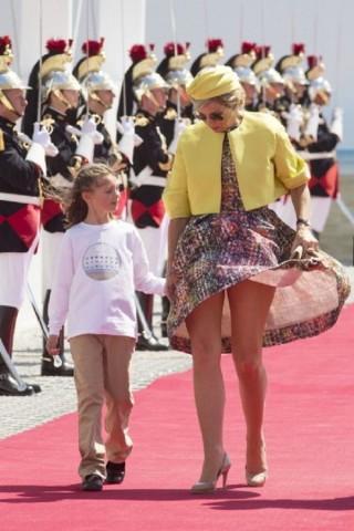 A bela Rainha Máxima da Holanda anda de mãos dadas no tapete vermelho com sua filha e é surpreendida pelo vento forte que levanta seu vestido estampado deixando a mostra um bonito par de pernas!
