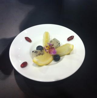 Prato de porcelana branca e bordas largas com fruta kiwi cortada em fatias grossas com limão siciliano fatiado finoe enfeitada com semente vermelha de fruta do milagre