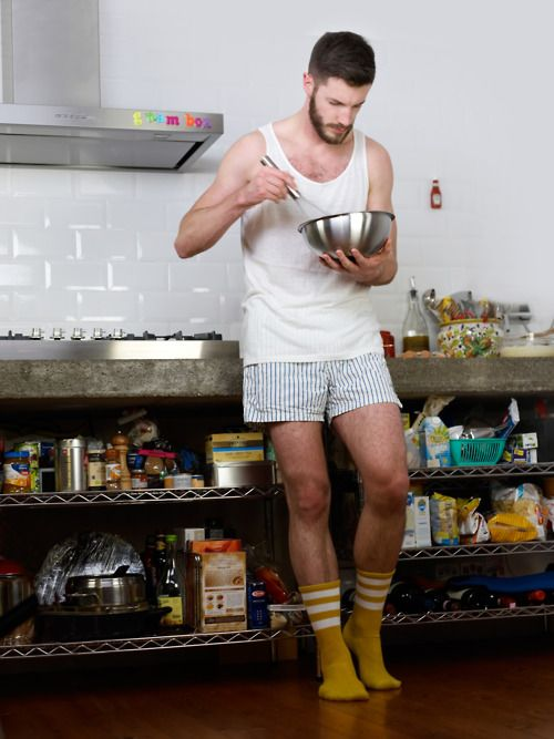 homem de frente, encostado num balcão de cozinha, repleto de condimentos, enlatados, farináceos, ela veste camiseta branca, cueca listrada branca, meias cor mostarda com listras brancas e está preparando alguma comida, num boll de aluminio.