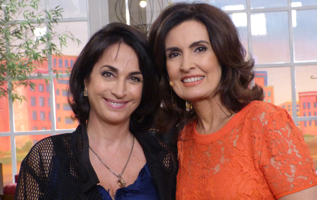 Claudia Matarazzo e Fátima Bernardes durante o programa Encontro com Fátima Bernardes - Claudia veste blusa azul bic e um casaquinho preto rendado, Fatima veste uma blusa cor coral, ambas estão sorrindo