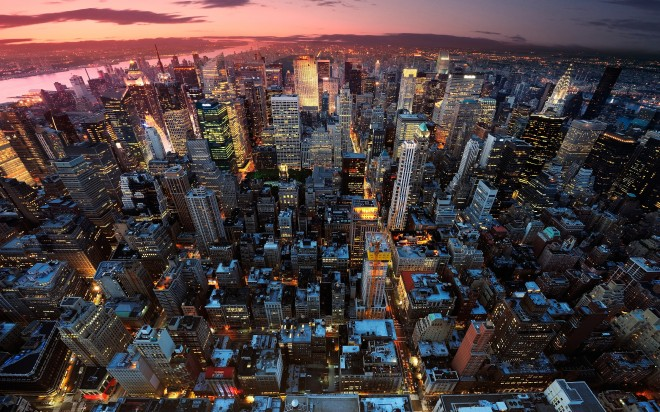 Vista do entardecer da cidade de Nova Yorque, em foto panorâmica, onde o sol ilumina ao fundo e as luzes do prédios iluminando os belíssimos e enormes edifícios.