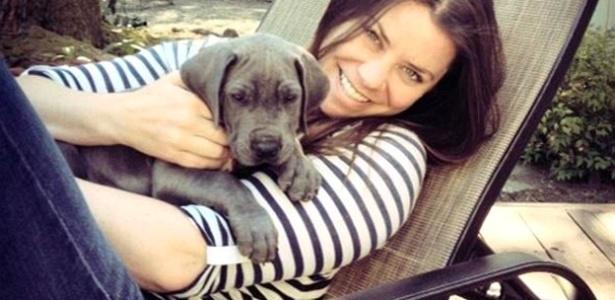 jovem bonita, de vinte e poucos anos, sentada em uma espreguiçadeira segurando uma labrador filhote cinza no colo. Ela sorri para a câmera.