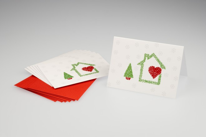 Cartão de Natal, na cor cinza, tendo ao centro um envelope vermelho e sobre ele um cartão com um desenho de uma casinha com um coração vermelho dentro dela e ao lado uma pequena arvore verde com caule na cor vermelha.