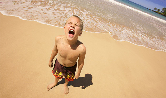 foto mostra um menino de aproximadamente 8 anos gritando de costas para o mar