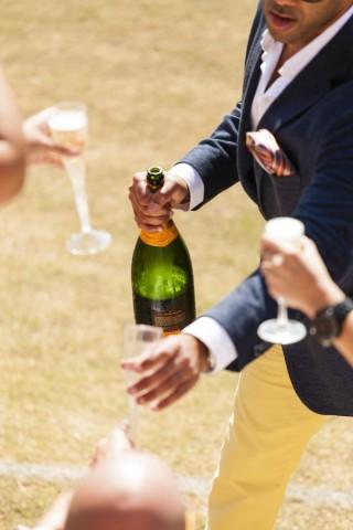 """Em ambiente aberto, um homem vestindo camisa branca e blaser azul, oferece champanhe Veuve Clicquot, onde aparece mãos de pessoas segurança a taça """"flute"""" com champanhe."""