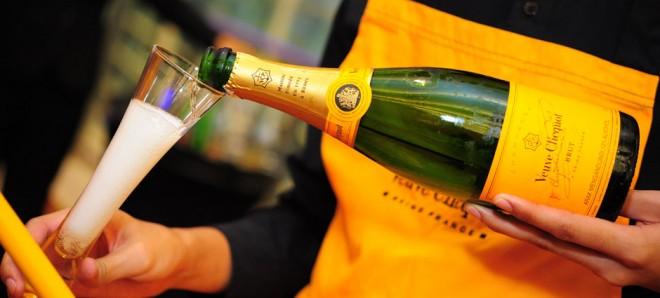 Uma pessoa vestindo avental laranja amarelado serve uma taça de champanhe, na mão direita ele segura a taça e na mão esquerda ele tem a garrafa de champanha Veuve Clicquot,