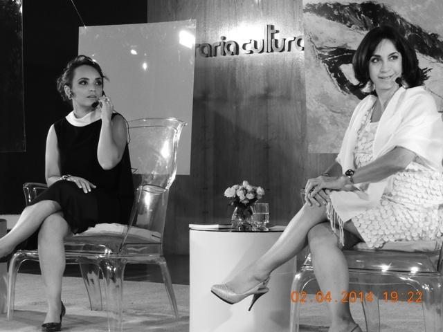 Foto em preto e branco, Claudia Matarazzo sentada numa cadeira no palco, junto com mulheres do Blog Observatorio Feminino .