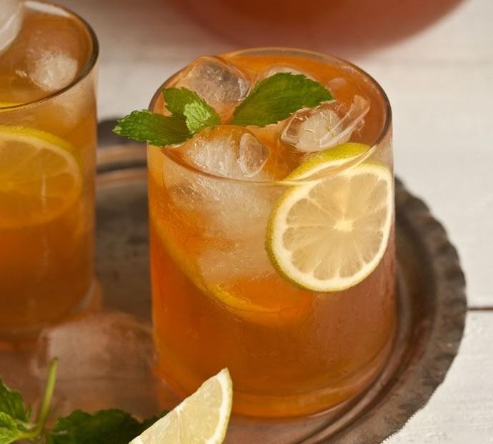 bandeja em prata, com 3 copos estilo drink, com chá gelado, decorados com rodelas de limão e folhas de hortelã nas bordas