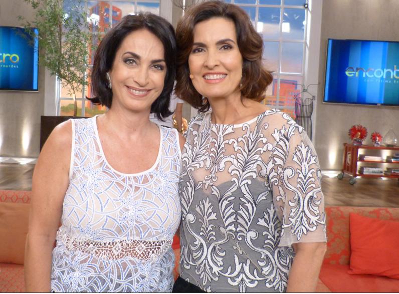 Claudia Matarazzo ao lado de Fátima Bernardes no Programa Encontro da Rede Globo, Claudia está a esquerda usando blusa rendada, na cor branca com detalhes em azul, e Fátima uma blusa transparente com detalhes bordados e um top preto por baixo.