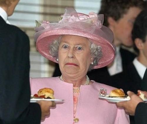 A Rainha Elizabeth II da Inglaterra de tailleur e chapéus cor de rosa claro faz uma cara de enorme espanto ao ver que duas pessoas lhe oferecem um prato com sanduíches altos ao mesmo tempo.