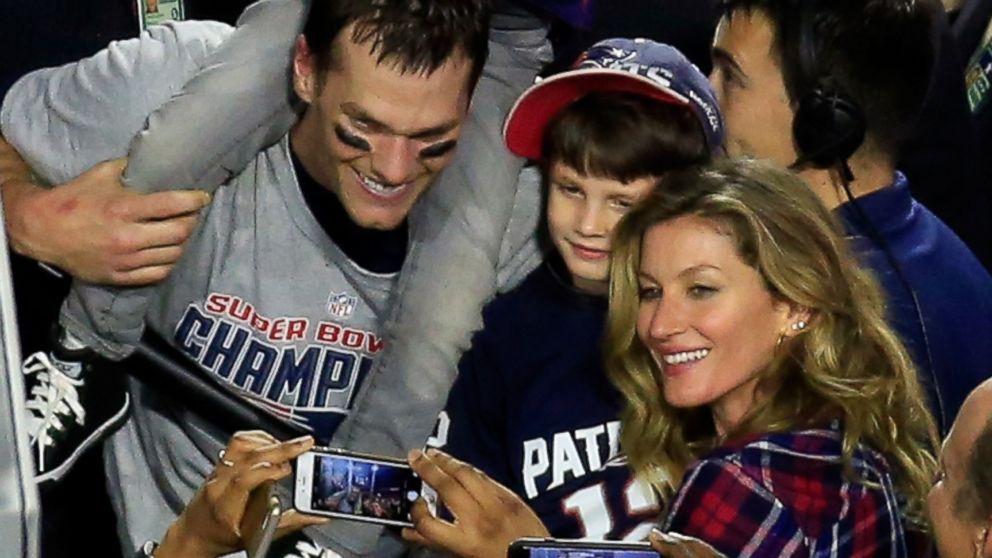 a foto mostra tom brady, gisele bundchem e o filho do casal no meio dos dois. ele está com uma criança nos ombros. todos felizes e sorrindo para foto na final do Super Bowl.
