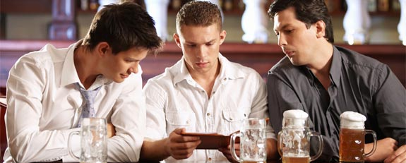 tres jovens sentados durante um happy-hour, examinam a conta do bar, os tres olhando fixo para o valor, diante deles tres canecas de chopps, uma cheia e duas quase vazias