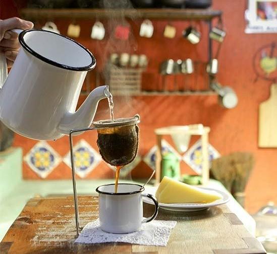 uma xícara de cafezinho de ágata branca está em primeiro plano com um bule também em ágata branco vertendo café fumegante em um coador de pano individual por onde o café passa e cai na xícara. Ao fundo percebe-se um ambiente de cozinha rústico e acolhedor com paredes pintadas de laranja .