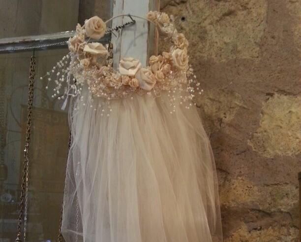 Girlanda de noiva com flores aparentemente de seda em tons de rosa claro e pêssego, com um véu de noiva está pendurada em um poste contra um muro de pedra.