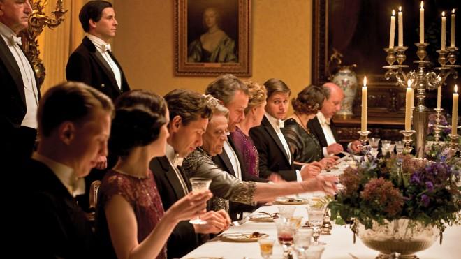 Em uma sal de jantar elegante na Inglaterra do início do século XX, os personagens da série inglesa Downton Abbey estão a mesa prontos para jantar. A mesa é oval com uma toalha creme e sobre ela taças de cristal e louça a frente de cada personagem. No centro um candelabro de cinco braços dá o toque final de requinte. O dono da Casa Lorde Crawley está de frente e atrás dele o mordomo impecável aguarda ordens em pé.a direita e esquerda de Lorde Crawley, estão sua filha Mary e a sobrinha Rose elegantemente trajadas e a sua frente estão sua mulher, sua terceira filha e o genro, todos concentrados em uma conversa aparentemente séria.