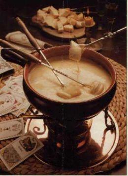 a foto mostra uma panela de fondue em cobre com 3 garfos de fondue com pão, mergulhados no queijo