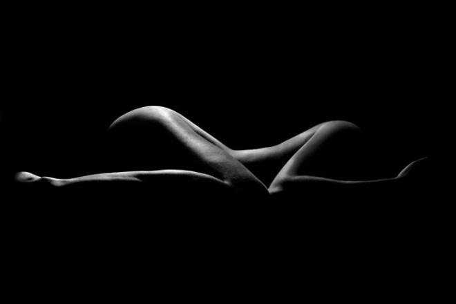 Silhueta de uma mulher adulta e curvilínea agachada no escuro com apenas uma fresta de luz delineando a lateral das nádegas, coxas, ombro o braços. A impressão é de leveza e mistério uma vez que não se enxerga o rosto e apenas partes do corpo bem feito desenhado pela luz.