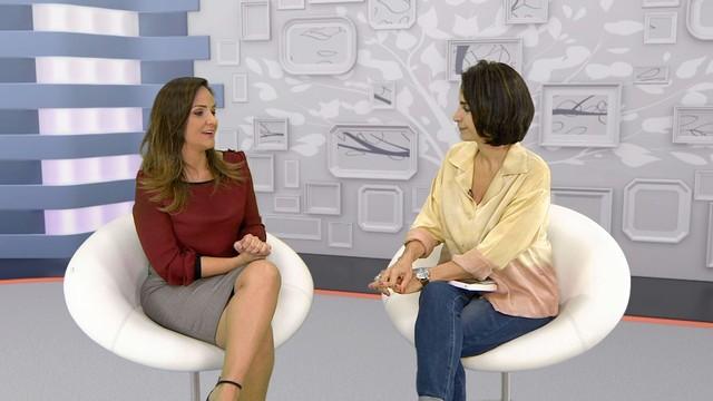 Claudia Matarazo, usando camisa clara em tons dourados e calça jeans, esta ao lado da jornalista Adriana Cutino, que veste saia cinza e blusa na cor marsala, ambos estão sentadas numa cadeira na cor branca, ao fundo cenário estilizado com desenhos geométricos em tons de cinza e gelo.
