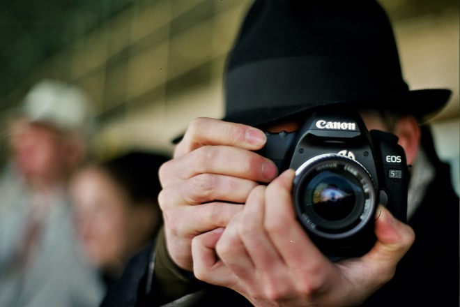 fotógrafo com a câmera fotográfica junto ao rosto focando a imagem. Ela usa um chapéu preto de feltro.