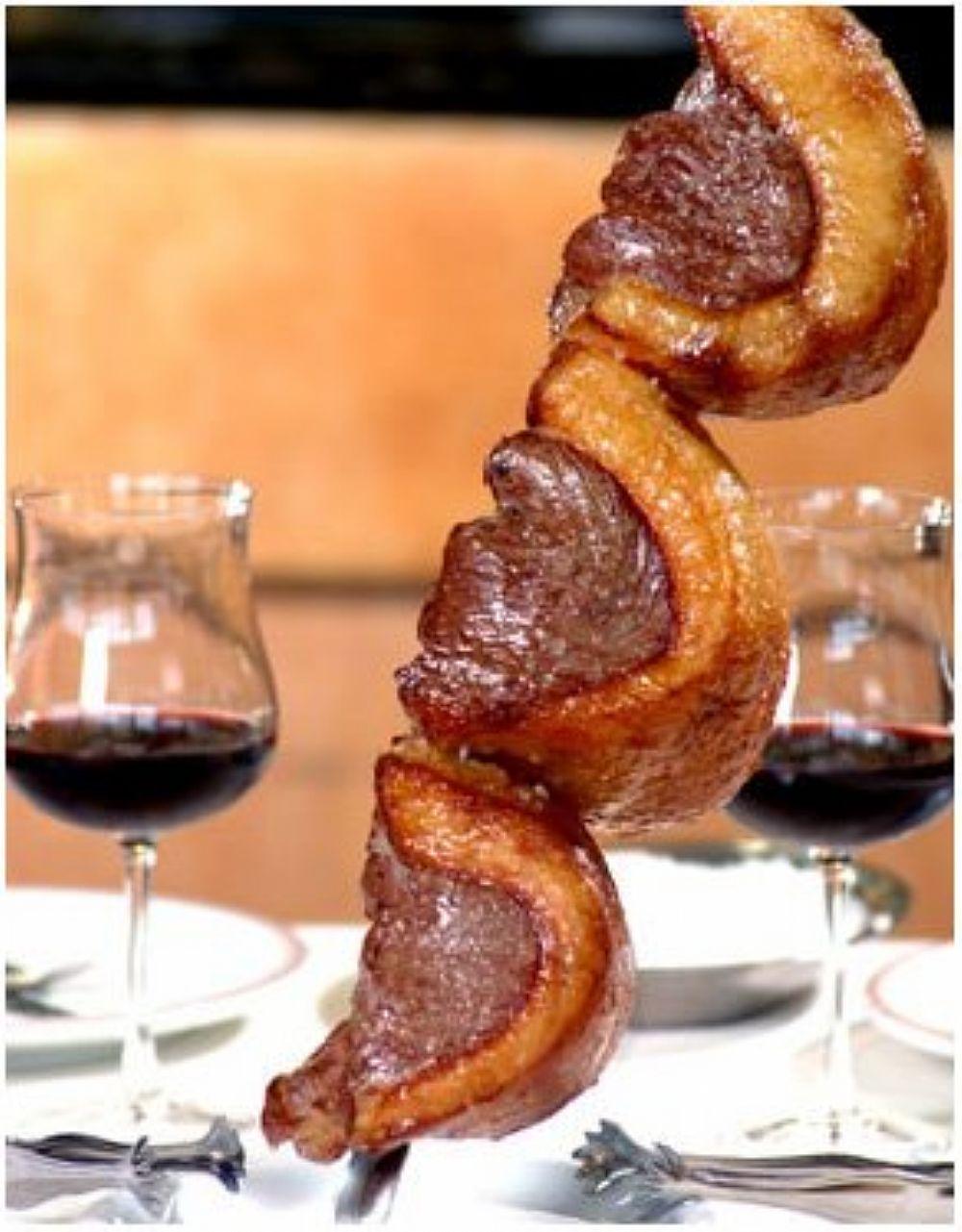 Espeto com 3 pedaços de picanha, apoiado com a ponta sobre a mesa ao lado de duas taças de vinho tinto.