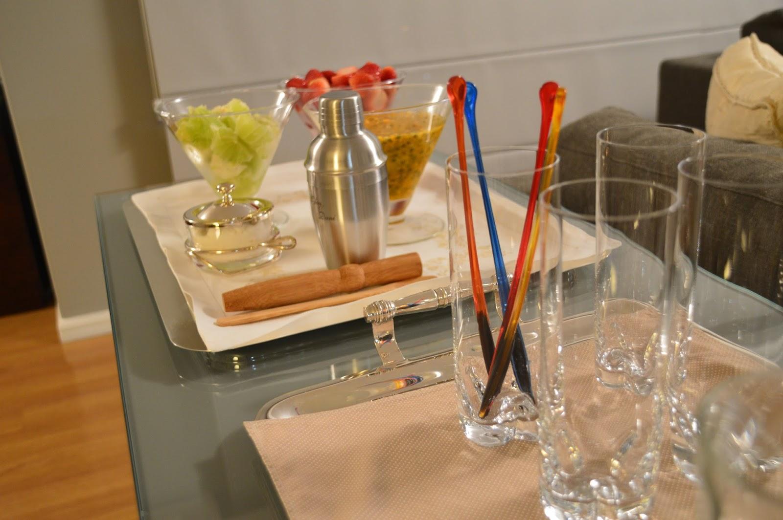 Sobre uma bancada, vários potes em vidro com pedaços de limões cortados, morangos cortados e outro com maracujás e coqueteleira para fazer drinks e vários copos