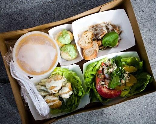 Caixa de papelão, com várias opções de pratos, contidas em potes de papel, com pães, saladas, , pote com sopa, e talheres de plástico