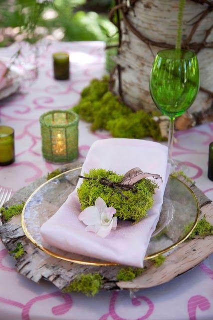 mesa de refeição, composta com toalha em tecido, branco com detalhes rosas, supla com franjas verdes, sobre o prato, guardanapo , na cor branca, e graveto com folhagem verdes e uma pequena flor branca, Ao lado uma taça de vidro verde, e num outro pequeno pote uma vela acesa.