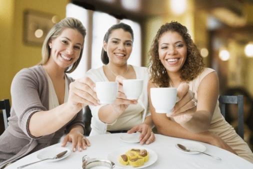 Tres mulheres estão numa mesa tomando cafes, a esquerda uma loira, ao centro uma de cabelo castanhos e a da direita com cabelos cacheados na cor castranho claro, todas as três seguram a xicara ao centro da mesa.