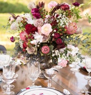 arranjo de flores em tons de rosas vermelhas e rosa, no centro de uma mesa de almoço toda montada.