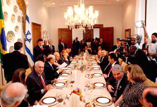 Almoço concedido ao Primeiro Ministro de Israel, Shimon Peres, na Ala Residencial do Palácio dos Bandeirantes em São Paulo, ele está sentado no centro da mesa ao lado do Governador. Outras 18 pessoas compõem a mesa. e muitos jornalistas filmam e fotografam a cena.