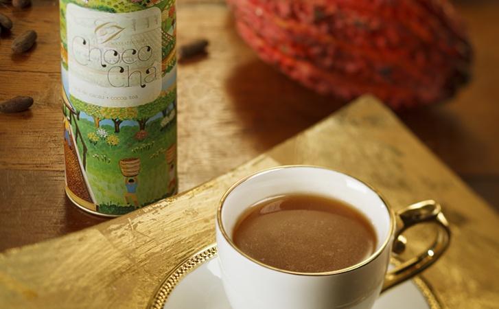 Uma xícara de chá em porcelana clara está em primeiro plano sobre um pires. Dentro, uma bebida que tem textura de chá e aparência de chocolate. Em segundo plano está uma latinha e formato cilíndrico com o rótulo colorido onde está estampada uma plantação de cacau.
