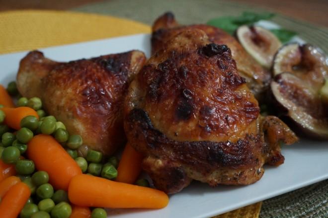 prato com pedaços de frango preparados, no mesmo prato, mini cenouras e ervilhas.