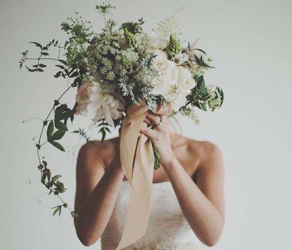 mulher usa vestido de noiva, estilo tomara que caia, ela segura um buquê de flores junto ao seu rosto.