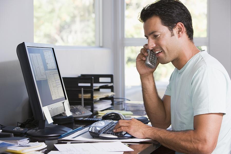 Um homem usando camiseta azul clara, está usando o celular diante de uma mesa de trabalho em casa. Sobre a mesa muitos papéis, canetas. Ao fundo , uma janela de vidro, onde temos um belo jardim