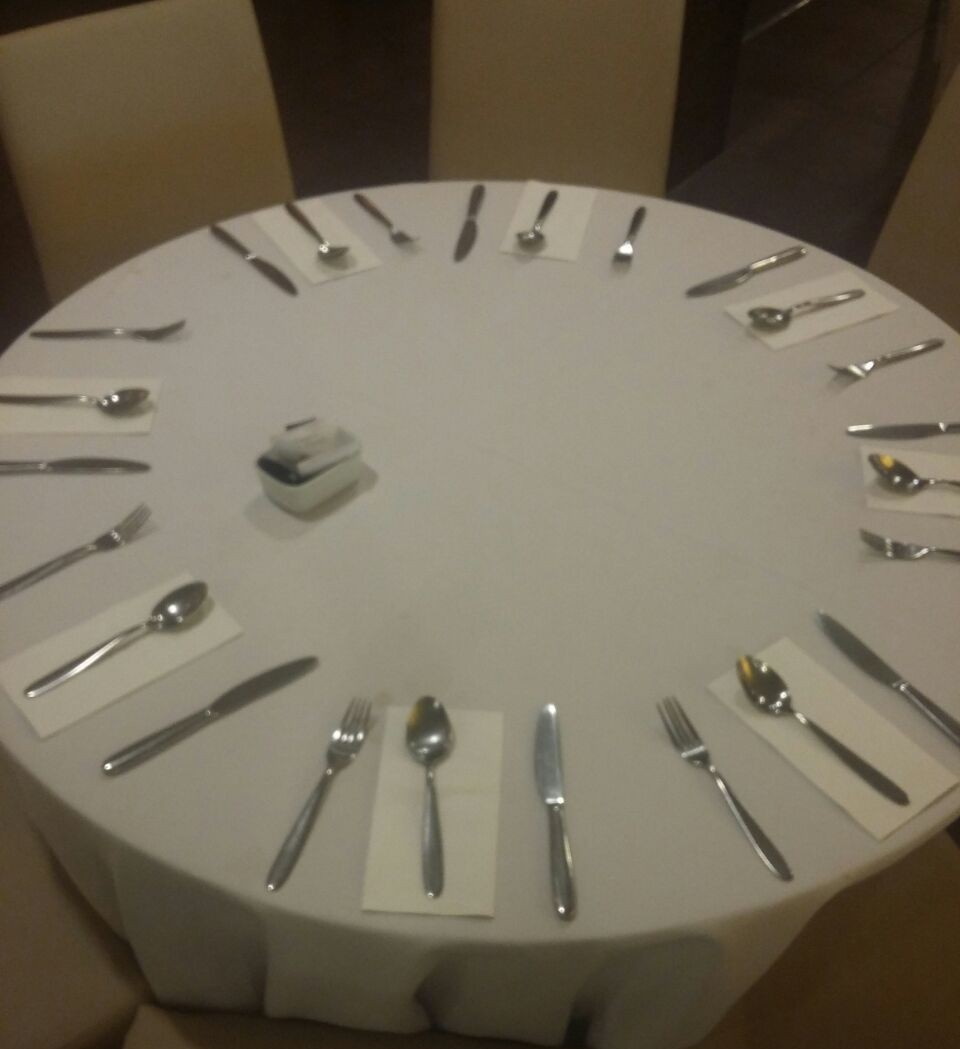 Visão superior de uma mesa redonda, com toalha, de cor clara, e os talheres posicionados : garfo, um guardanapo, sobre ele uma colher e segue-se uma faca. Repete-se o mesmo padrão por toda a mesa. ao centro um pequeno porta temperos