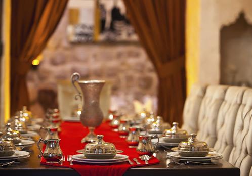 Uma mesa retangular colocada com toalha vermelha e cerca de 8 ou 9 pratos com a uma colhe de prata por cima de cada um deles estão enfileirados simetricamente . Ao fundo uma jarra de prata trabalhada completa o visual.