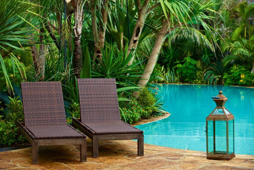 Detalhe da piscina do Hotel Lara, Aquiraz, Ceará, onde temos duas cadeiras de descanso, em madeira, ao fundo um lindo jardim com palmáceas.
