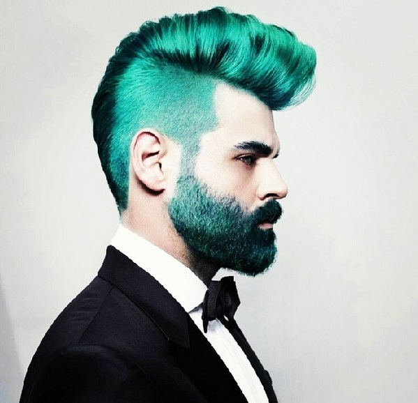 Imagm em lateral de um Homem jovem, usando roupa black-tie, paletó cor preta, camisa social, cor branca e gravata borboleta, cor preta e usa barba e cabelos ralos na cor azul.