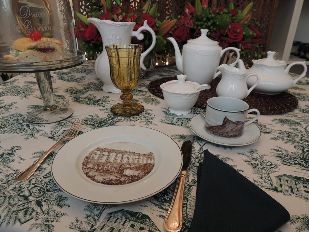 xícara de chá, da coleção Francesca Romana, da porcelana schmidt, com detalhes da paisagem do Rio de Janeiro em sépia. Ao fundo uma jarra em porcelana branca, e um copo de vidro amarelado, com água.