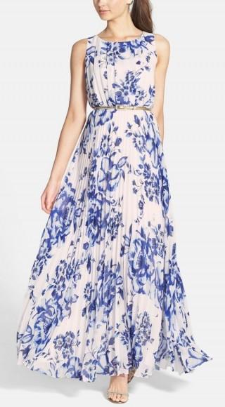 modelo usa vestido longo com fundo branco estampado em flores azul royal. O modelo é rodado e sem mangas.