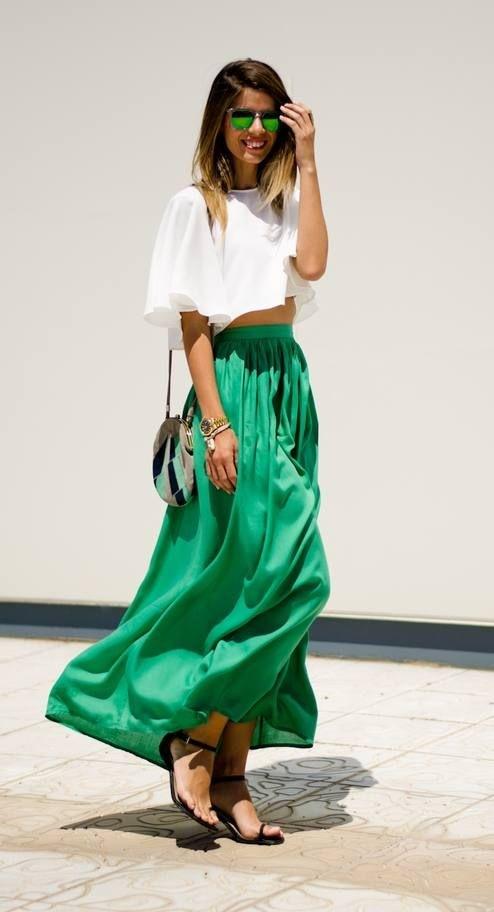 Moça de cabelos castanhos na altura dos ombros usa saia longa verde e rodada com mini blusa branca de mangas largas modelo morcego. Os óculos escuros são igualmente verdes iguais a saia e ela usa sandálias de tiras finas e salto baixo.