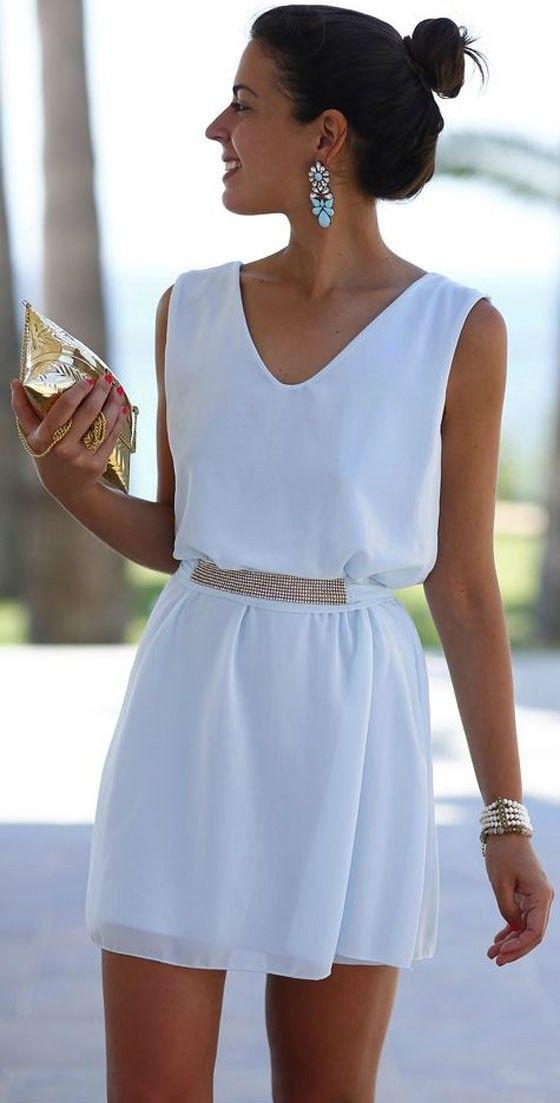 modelo de cabelos escuros e presos displiscentemente em um coque alto usa um vestido curto com cinto fino de pedras brancas brilhantes e um brinco de pedras azuis e brancas.