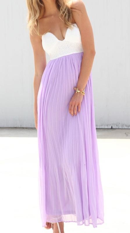 Modelo com o rosto parcialmente coberto e cabelos logos e louros usa vestido tomara que caia com a saia plissada lilás na altura dos tornozelos. A parte de cima faz contraste com o lilás pois é branca e realça o bronzeado da moça.