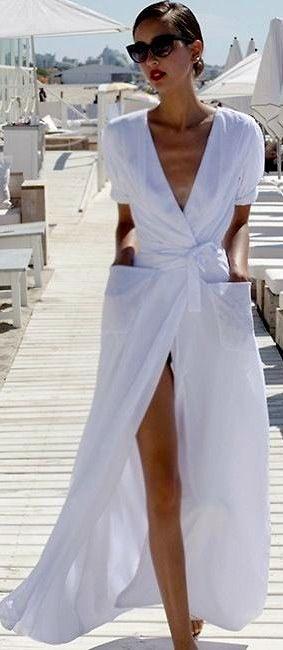 moça de cabelos castanhos presos em coque e óculos escuro usa vestido de algodão branco de mangas curtas longo.Apesar de longo o decote em V profundo, as mangas curtas e a fenda na frente passam a sensação de frescor e informalidade
