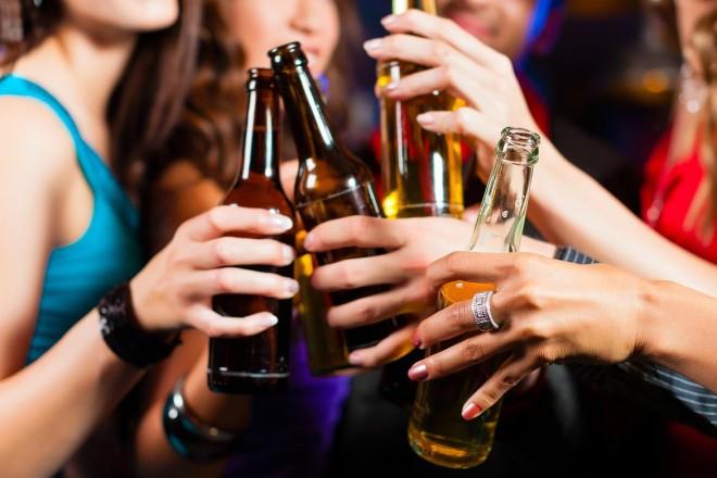 várias pessoas seguram uma garrafa do que aparenta ser cerveja com as mãos próximas. Na foto, visível apenas as mãos