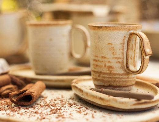 prato em cerâmica com pó de canela e pau de canela ao lado xícaras de cerâmica, alta e na cor de creme com manchas na cor marrom.