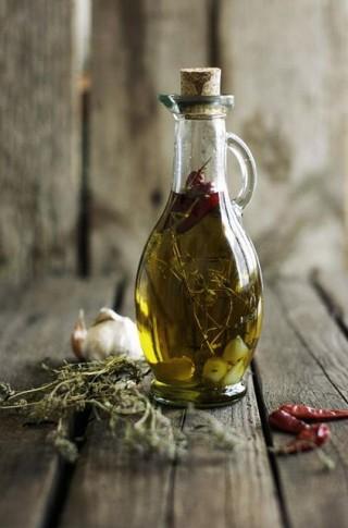 Sobre um engradado de madeira uma garrafa de vidro transparente com azeite de oliva e algumas ervas e pimenta. Ao lado da garrafa, algumas ervas , uma cabeça de alho e 3 pimentas dedo-de-moça