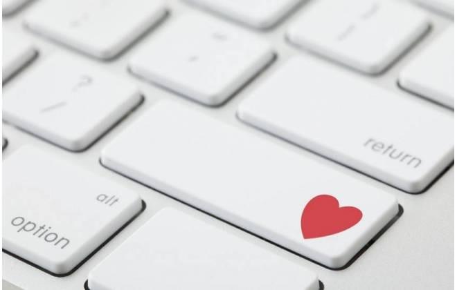 """imagem em detalhe de um teclado de notebook, on a tecla """"Enter"""" tem um símbolo do coração, na cor vermelha. Simbolizando que a pessoa está se relacionamento pela internet."""